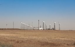 Onshore wind farm, using several horizontal axis turbines, summer day Royalty Free Stock Photo
