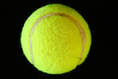 Green tennis ball on black background Royalty Free Stock Photos