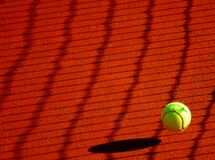 Green Tennis Ball on Red Floor during Sunny Day Royalty Free Stock Photography