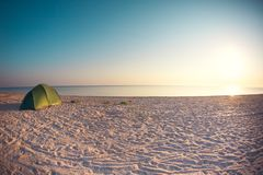 Tent on the beach. Green tent on the beach. Sunset on the sea coast. Camping on the shore of the ocean Stock Photos