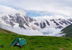 Green tent in beautiful mountains landscape. Green tent on the grass in snowy beautiful mountains landscape with amazing foggy clouds. Evening camp in russian royalty free stock photo
