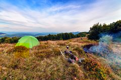 Tent and campfire in mountains Stock Image