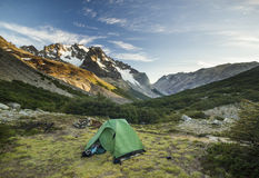 Green tent in mountains at sunrise. Green  tent on grass with snow-covered surrounding mountains at sunrise Royalty Free Stock Image