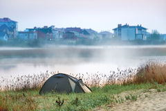 Green tent near river with morning mist Stock Photos