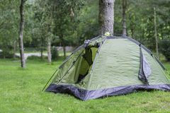 Green tent pitched near tree. Small green tent pitched near tree on camping in rural England.Tourism in UK.Outdoors equipment.Vacation on British countryside royalty free stock image