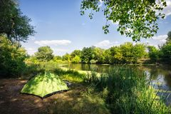 Green tent on the riverbank under blue sky Royalty Free Stock Photography