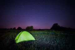 Green tent under the starry sky in the field Stock Image