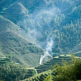 Green terraced field and smoke Royalty Free Stock Image
