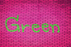 Green text on brick wall pink Background Royalty Free Stock Photography