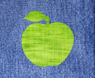 Green textile apple with leaf over blue jeans texture background. Green textile apple with leaf over blue jeans texture  as background Stock Photo