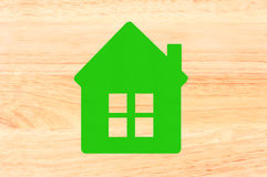 Green textile house symbol over wooden texture close-up Stock Images