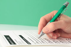 Green Themed Pen in Hand Completing Form Stock Photos