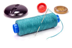 Green thread on a plastic spool with needle and buttons on white background Stock Photos