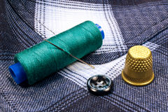 Green thread on a plastic spool with thimble and a button on the background of the shirt Royalty Free Stock Photo