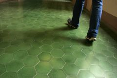 Green Tile Floor in an Ancient Building. Lady walking on bright green tiles in hexagon shape royalty free stock photo