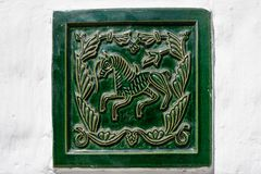 Green tile on white wall Stock Image