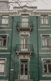 A green-tiled townhouse in Lisbon, Portugal. A front of a green-tired townhouse in Lisbon, Portugal. The image was taken in January 2017 on a cloudy winter day Stock Images