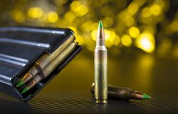 Green tipped AR-15 ammo and magazine. Loaded magazine and cartridges for an AR-15 on a yellow background Stock Photo