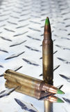 Green tipped rifle shells on chrome metal Stock Photos