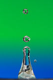 Green to blue water drop. Drop splashing before blue and green background Royalty Free Stock Photos