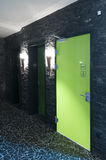 Green toilet door. Toilet door made of plexi glass in a swimming pool with dark tiles and flambeus as light Stock Images