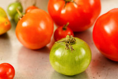 Green Tomato With Red Tomato Background Stock Photos