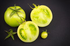 Green tomatoes on dark backgeround. Sliced raw green tomatoes on dark backgeround Royalty Free Stock Images