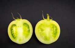 Green tomatoes on dark backgeround. Sliced raw green tomatoes on dark backgeround Royalty Free Stock Photography