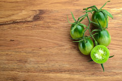 Green tomatoes. Fresh grape green tomatoes for use as cooking ingredients with a halved tomato in the foreground with copyspace. Top view Stock Photography