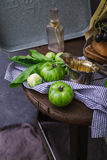 Green tomatoes and grapes on rustic background. Dark food photography concept Stock Photo