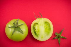Green tomatoes on red backgeround. Sliced raw green tomatoes on red backgeround Royalty Free Stock Image