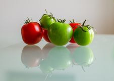 Green and red tomatoes with reflection. Green tomatoes with reflection on the glass table Royalty Free Stock Image