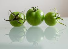 Green tomatoes with reflection. On the glass table Royalty Free Stock Photography