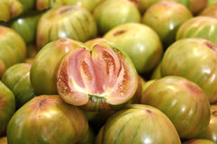 Green tomatoes for salad on counter market. Large green tomatoes for the salad on the counter market stock image