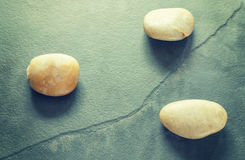 Green toned three stones on a cracked slate. Stock Photos