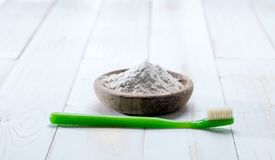 Green toothbrush in foreground with user friendly baking soda. Green toothbrush in the foreground with user friendly baking soda powder in wooden cup for natural Royalty Free Stock Images