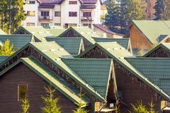 Green tops of the roof of new residential wooden houses. Royalty Free Stock Photo