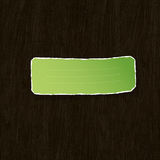 Green torn label on wooden texture. Royalty Free Stock Photos