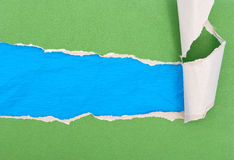 Green torn paper on blue paper Royalty Free Stock Image