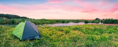 Green tourist tent on the river bank at dawn Stock Image