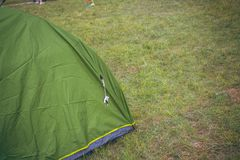 Green touristic tent among grass , on grassland, forest camp Royalty Free Stock Images