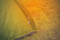 Green touristic tent among grass , on grassland, forest camp Stock Image