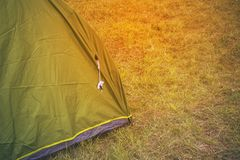 Green touristic tent among grass , on grassland, forest camp Royalty Free Stock Image