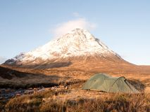 Green touristic tent on meadow at river below snowy cone of mountain Stob Dearg 1021 metres high Stock Photo