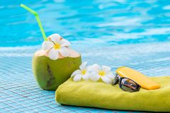Green Towel And Beach Accessories Near To A Juicy Coconut Decorated With Flowers On The Edge Of The Pool Stock Photos