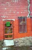 Green towel and building. Old slum lord building with red orange faded and weathered old paint and green towel on board in slum and inner city core of Milwaukee royalty free stock image