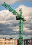 Green tower crane on a background of clouds stock photo