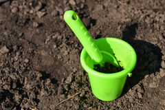 Green toy bucket and spade in mud Royalty Free Stock Photo