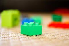 Green toy building block with defocused background. Isolated green plastic toy building block with defocused background stock photo
