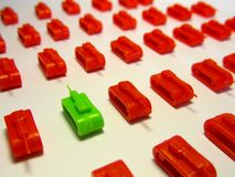 Green toy tank opposite to rows of red toy tanks to symbolize Brexit and political clash. Landscape format stock photo